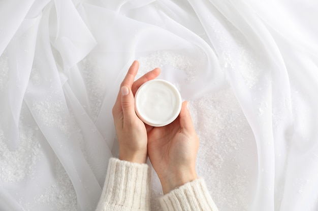 Woman holding jar of winter cream for skin, decorative snow on white fabric background, top view. space for text