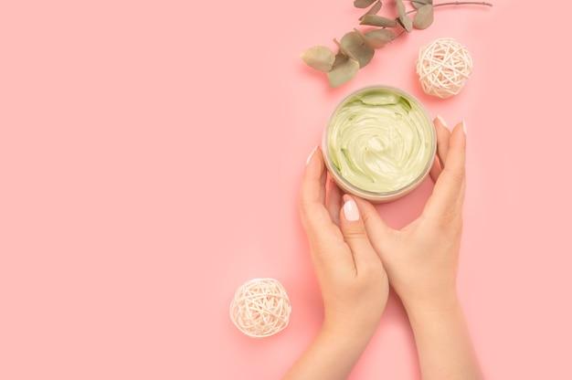 クリーム色と緑の葉の瓶を保持している女性。女性の手はピンクのテーブルに化粧品の保湿クリームローションを適用します。クリームの瓶を手に持った女性が若返りのきれいな肌。コピースペース