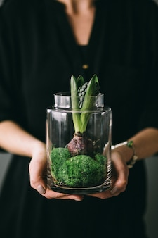 A woman holding a jar with a seedling