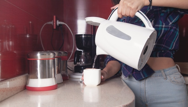 Woman holding kettle and pouring water into cup. preparing hot drink