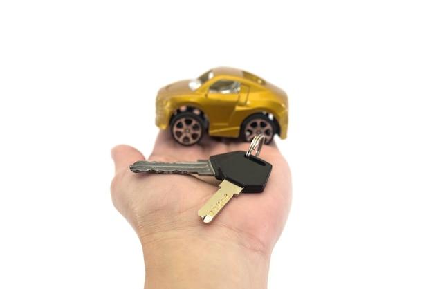 キーと白い背景の上のミニチュア自動車モデルを保持している女性、クローズアップ。車の購入