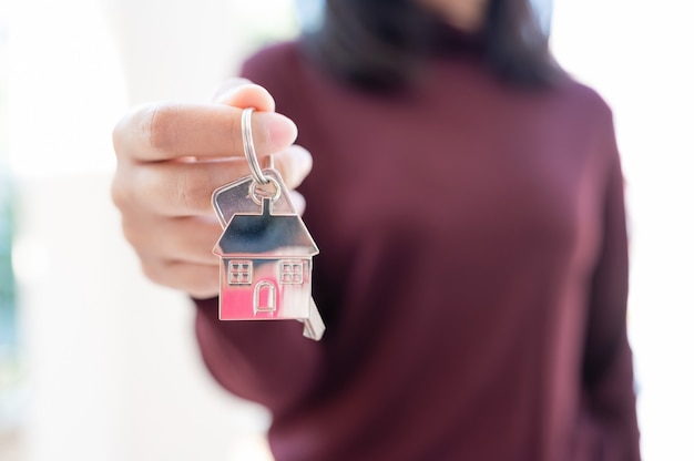 Woman holding keychains house key. property investment and house mortgage financial real estate concept
