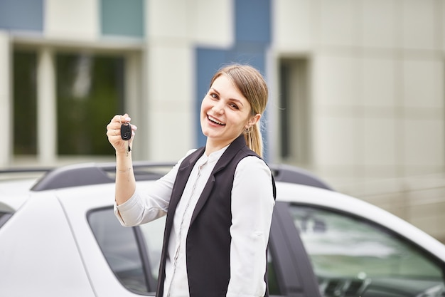 Woman holding keys to new car auto and smiling