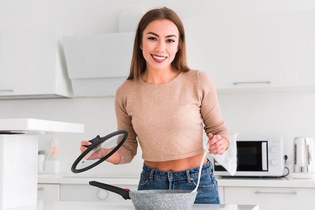 Oggetti della cucina della tenuta della donna nella vista frontale delle mani