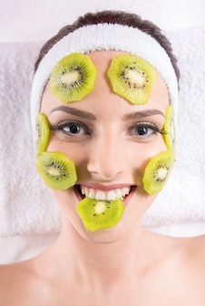 Woman holding kiwi fruit slices on the face in spa salon.