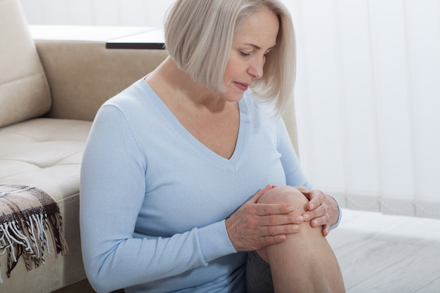 Woman holding knee with hands and suffering from pain at home