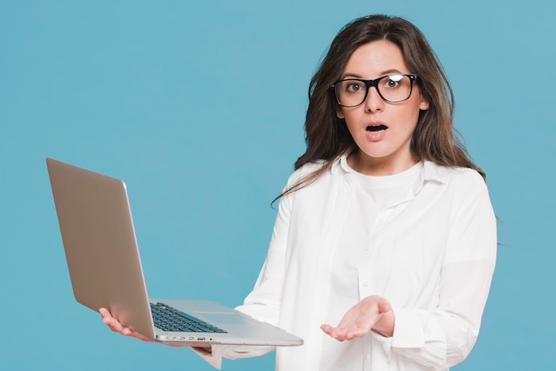 Woman holding a laptop and being surprised