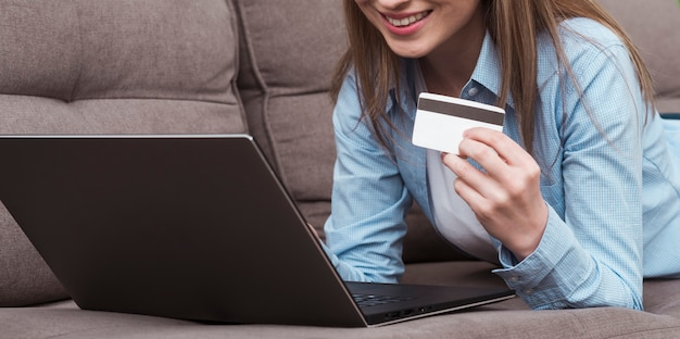 Woman holding laptop and credit card front view