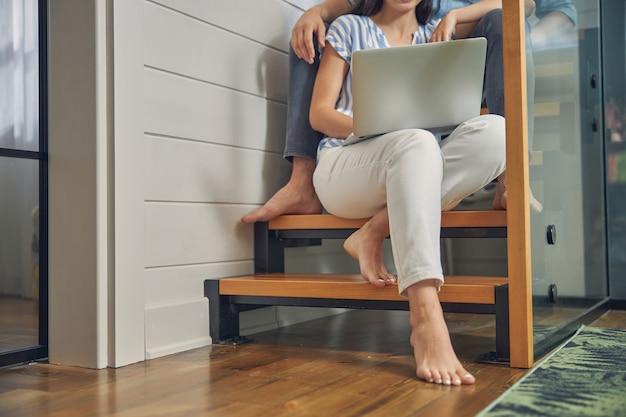 아름다운 집에서 계단에 앉아있는 동안 다리에 노트북을 들고 여자