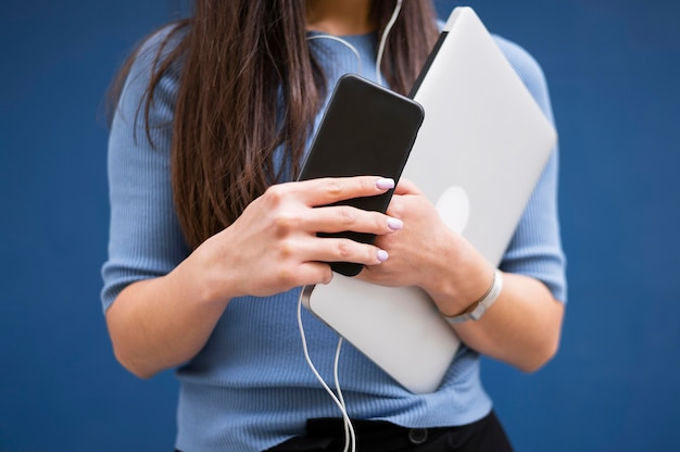 Woman holding laptop and smartphone with earphones
