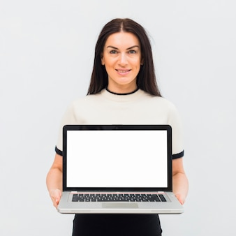 Woman holding laptop with blank screen
