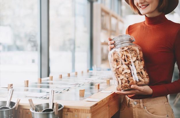 플라스틱 없는 식료품점 제로 웨이스트 샵에서 식료품이 든 큰 유리 항아리를 들고 있는 여성