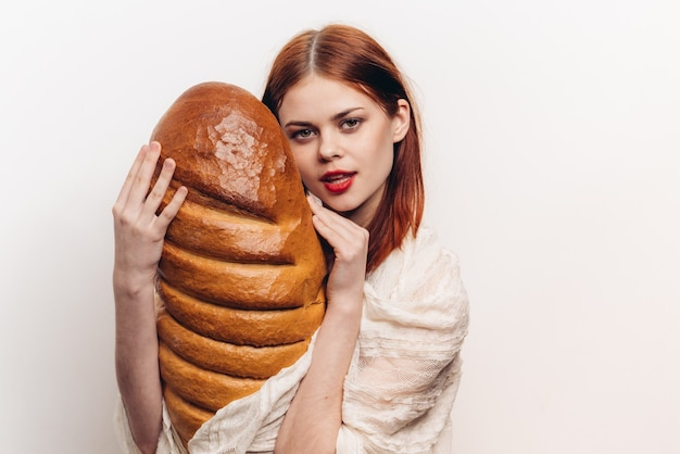 Woman holding a large loaf and bright makeup in her hands light clothing model.