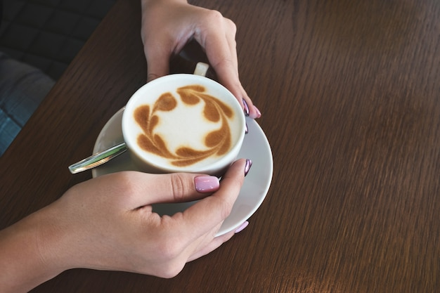Woman holding a latte coffee cup in cafe.