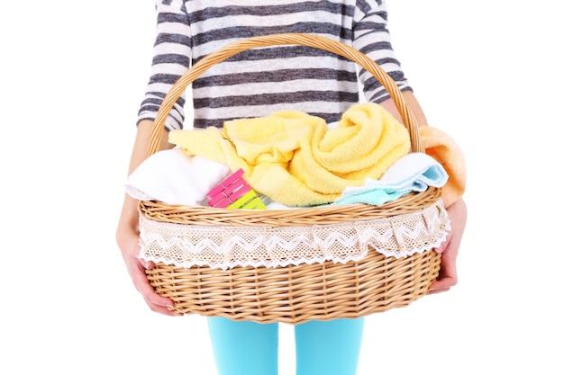 きれいな服、タオル、ピン、白で隔離の洗濯かごを保持している女性