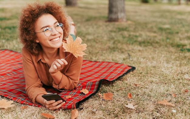 Donna che tiene una foglia e il suo telefono mentre si sta su una coperta