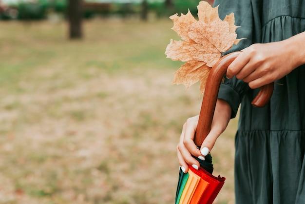 Donna che mantiene le foglie e un ombrello colorato con copia spazio