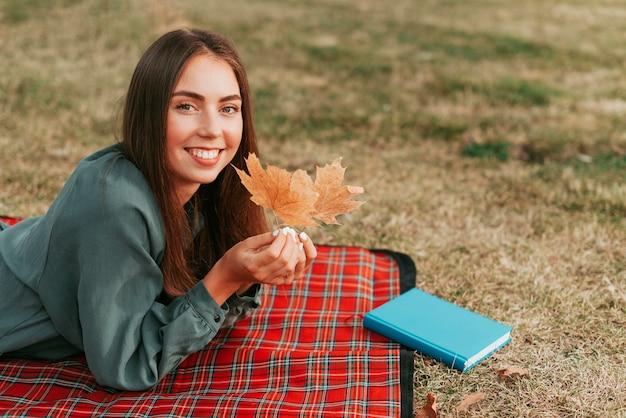 ピクニック毛布に葉を保持している女性