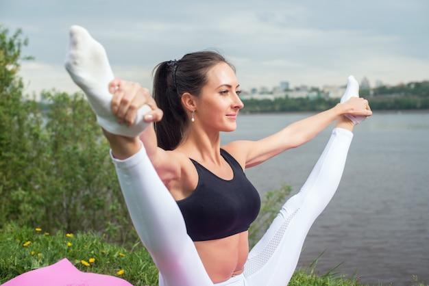 足を離して保持している女性は、体操でウォーミングアップするエアロビクスを行い、屋外でのストレッチ脚の柔軟性を高めます。