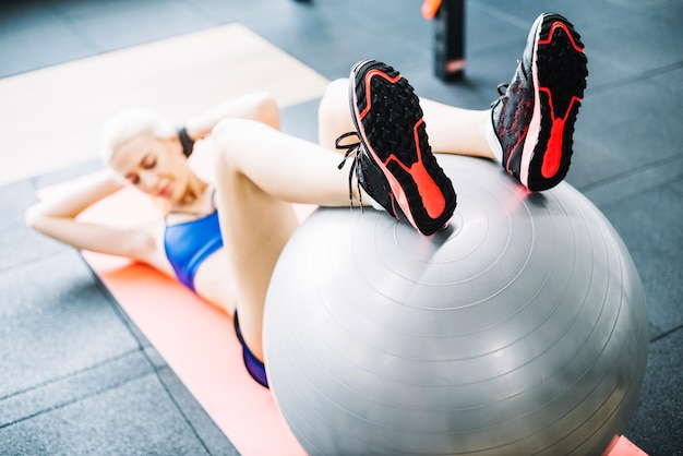 Woman holding legs on fitball