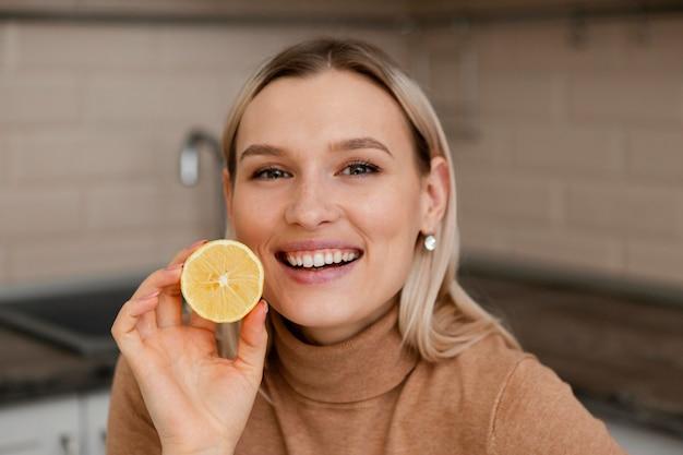 레몬 슬라이스를 들고 여자를 닫습니다.