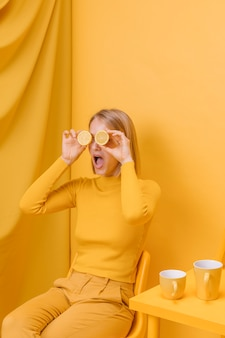 Woman holding lemons in front of eyes in a yellow scene