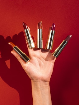 Woman holding lipsticks on her fingers