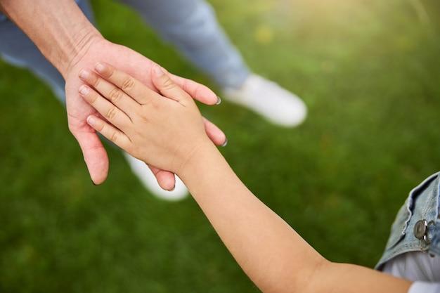 도시 공원에서 산책하는 동안 작은 손으로 그녀의 딸을 잡고 여자