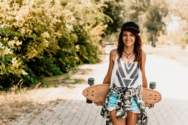 Woman holding longboard behind her back.