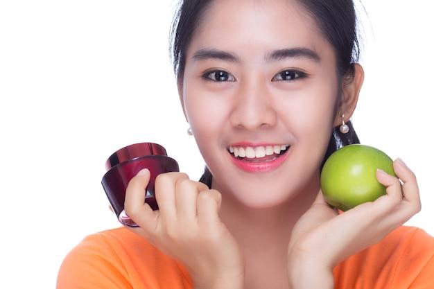 白い背景の上のローションクリームとリンゴを保持している女性。