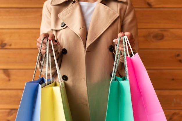 Женщина держит много красочных сумок