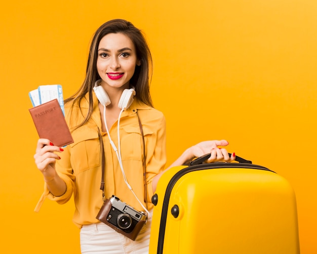 Woman holding luggage and passport with plane tickets