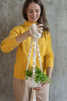 Woman holding macrame plant hanger with houseplant over yellow sweater