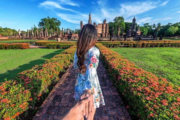 Женщина держит мужчину за руку и ведет его к храму ват махатхат на территории исторического парка сукхотай.