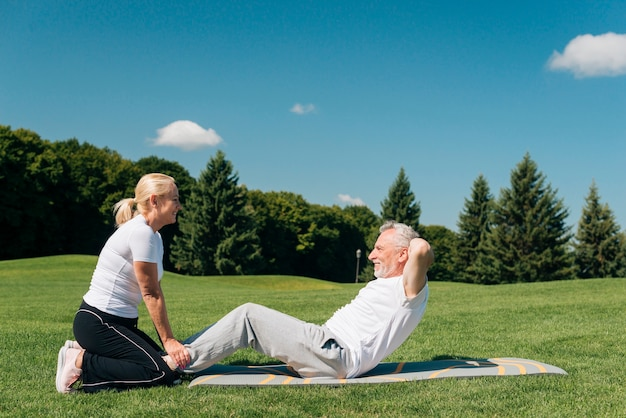 Woman holding man while he is doing crunches