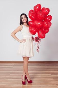 Женщина держит много воздушных шаров в форме сердца
