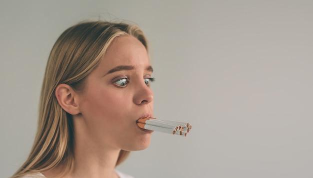 Женщина держит много сигарет во рту