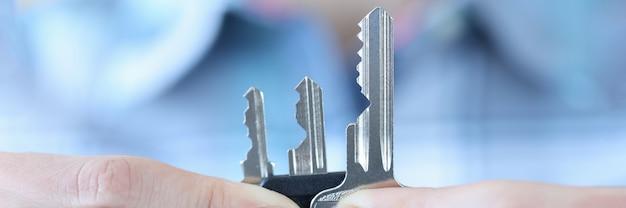 Женщина, держащая много металлических ключей в руках крупным планом, производство ключей концепции