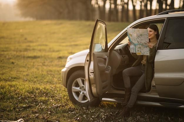 車のフルショットで地図を保持している女性