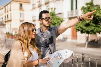 Woman holding map looking at her boyfriend pointing finger