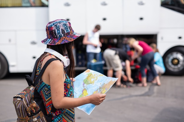 Woman holding a map at the train station tourism concept