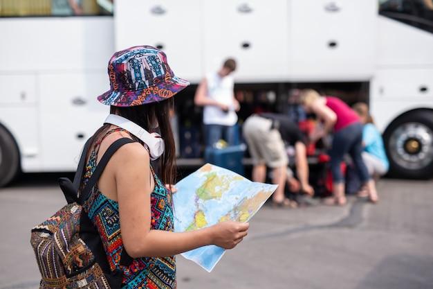 Donna che tiene una mappa presso la stazione ferroviaria concetto di turismo