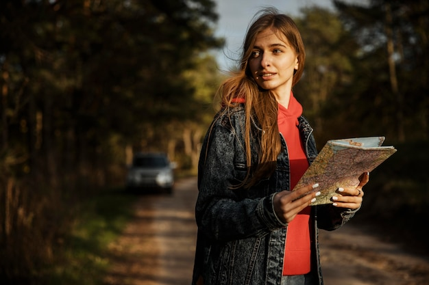 Donna che mantiene la mappa durante un viaggio su strada