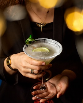 Woman holding a margarita glass garnished with lime