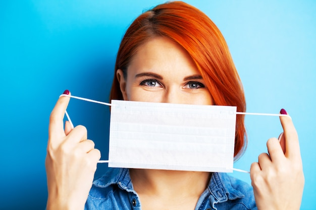 Woman holding mask to cover mouth and nose to protect against virus on blue background