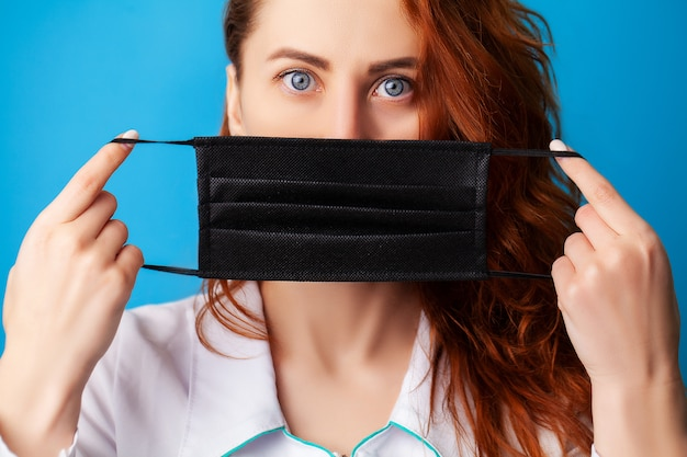 Woman holding mask to cover mouth and nose to protect against virus on blue background.