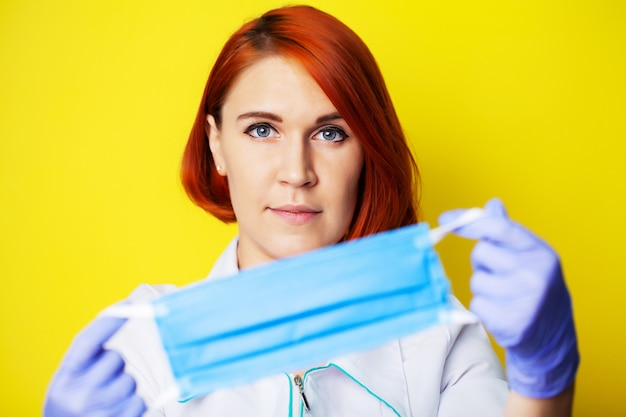 Woman holding mask to cover mouth and nose to protect against virus on yellow background