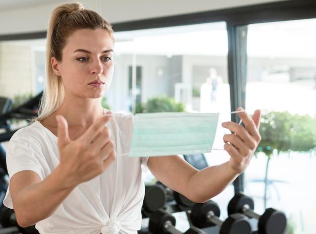 체육관에서 의료 마스크를 들고 여자