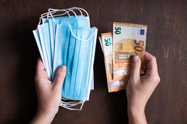 Женщина, держащая медицинские маски и деньги