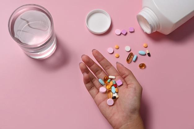 手に薬を持っている女性。